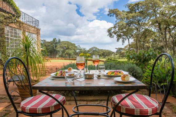 Giraffe Manor has beautiful manicured gardens and an outside terrace where guests can have lunch